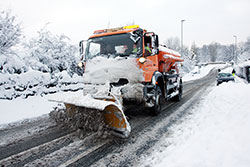gritter in snow with plough and car