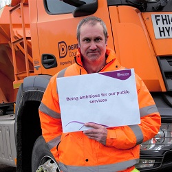 gritter worker holding council sign
