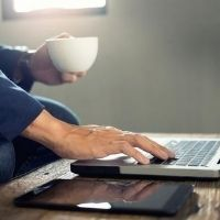 Man working on laptop holding a mug